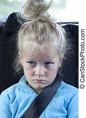 Grumpy kid with seatbelt in car - A sulky child in the back...