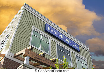Immediate Care Sign On Hospital Building with Clouds -...