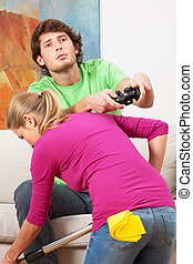 Woman cleaning the house and her husband with console -...