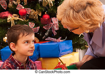 Grandma and grandson with christmas tree - Grandma giving...