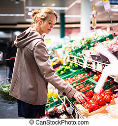 Pretty, young woman shopping for fruits and vegetables -...