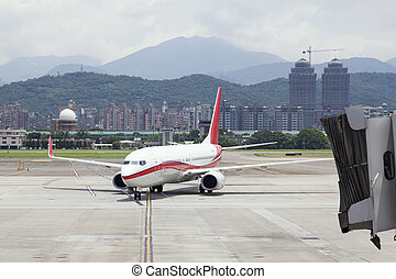 approaching aircraft with jetbridge in Taipei SongShan...