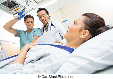 Medical Team Preparing Patient For Xray - Doctor and nurse...