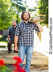 Portrait of mid adult carpenter and coworker carrying wooden...