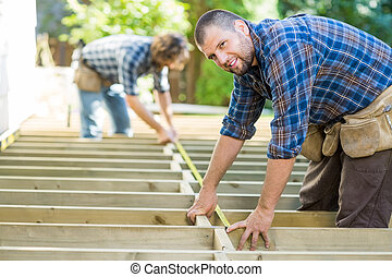 Carpenter Measuring Wood With Tape While Coworker Assisting Him