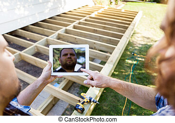 Carpenters Using Digital Tablet At Construction Site