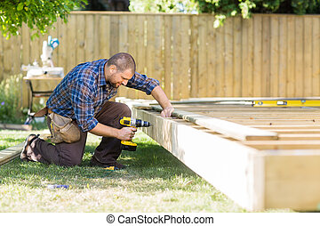 Carpenter Drilling Wood At Construction Site - Full length...