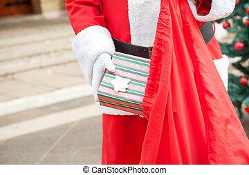 Senior Man Dressed As Santa Claus Putting Gift In Bag -...