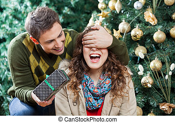 Man Surprising Woman With Gift In Christmas Store - Young...