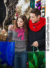 Couple Shopping In Christmas Store - Happy young couple with...