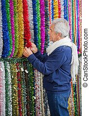 Senior Man Shopping For Tinsels - Senior man shopping for...