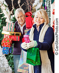 Woman Shopping Christmas Presents With Man - Happy senior...