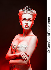 Red Queen with a crown and a corset, with make-up in studio...