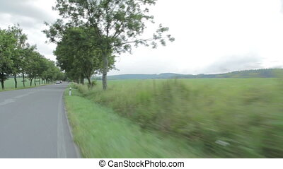 driving a car along a country road, meet cyclist and cars in...