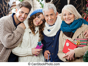 Happy Loving Family Standing In Christmas Store - Portrait...