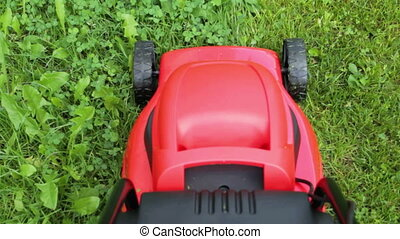 new lawnmower cutting green grass in cloudy day