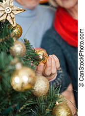 Couple Selecting Baubles Hanging On Christmas Tree At Store...