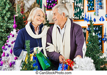 Happy Senior Couple Shopping In Christmas Store - Happy...