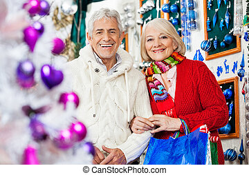 Couple With Shopping Bags Standing At Christmas Store -...