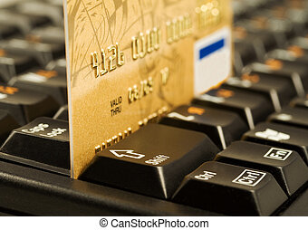 Gold credit card on computer keyboard Internet shopping...