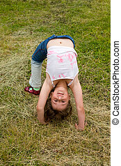 Bending over backwards - Little smiling girl-gymnast bends...