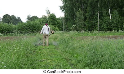 man trimmer cut grass - Man with trimmer cuts grass on...