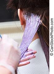 hairdresser applying color female customer at salon, doing...
