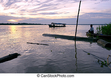 Amazon river landscape & people at sunrise, near Leticia...