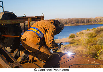 Welder at work. Construction of a bridge across the river