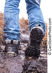 Walking hiking shoes on a muddy terrain with legs wearing...