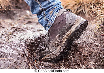 Side view of an hiking shoe covered in mud - Side view of a...