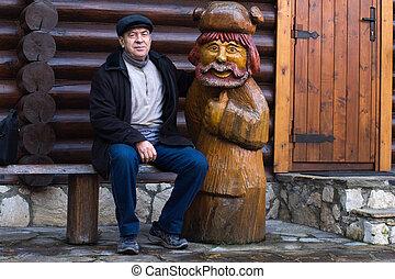 Elderly man sitting close to a wooden statue - Elderly man...
