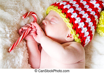 Newborn Christmas baby girl in elf hat on a white blanket