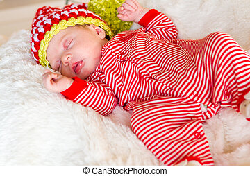 Newborn Christmas baby girl in elf hat on a white blanket.