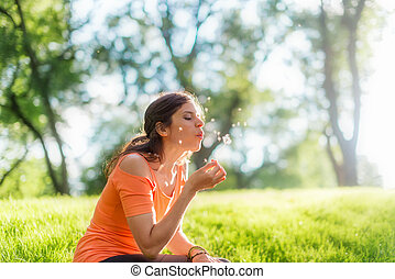 Portrait of girl in nature blowing a dandelion