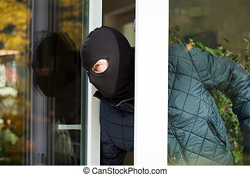 Housebreaker wearing a mask loking through the window
