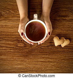 woman holding hot cup of tea with cookies on wooden table