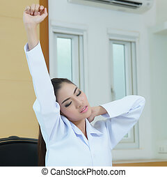 Tired female doctor stretching, Model is Asian woman