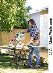 Carpenter using Table Saw - Carpenter using table saw while...
