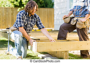Workers Working On Wooden Frame At Construction Site - Mid...