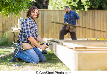 Confident Worker Drilling Wood At Construction Site -...