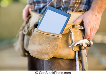 Digital Tablet And Hammer In Carpenters Tool Belt - Closeup...