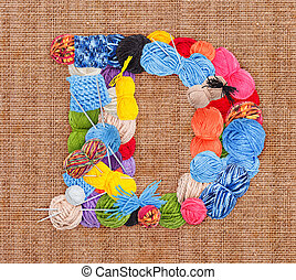 Letter D made of knitting yarn on burlap background