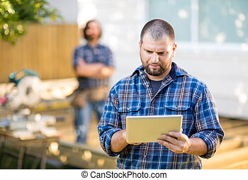 Mid adult manual worker using digital tablet with coworker...