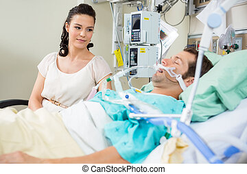 Woman Looking At Patient Resting On Bed - Beautiful woman...