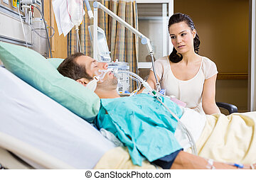 Woman Looking At Critical Patient Lying On Bed - Worried...