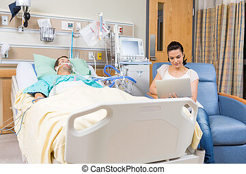 Woman Using Digital Tablet While Sitting By Patient - Young...