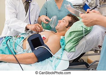 Doctor And Nurses Examining Critical Patient - Doctor and...