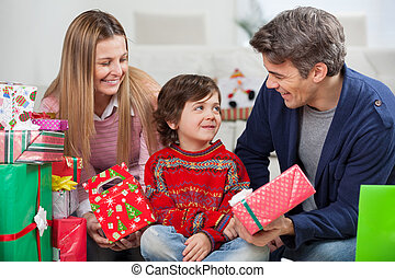 Parents With Christmas Presents Looking At Son