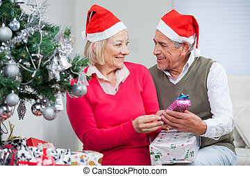 Couple With Christmas Gifts Looking At Each Other